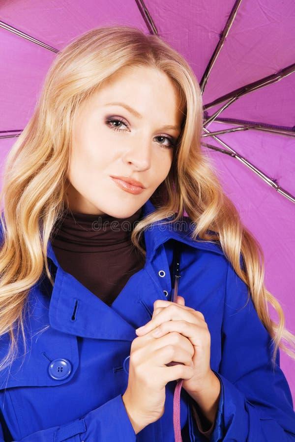 Modello grazioso in cappotto blu con un ombrello immagini stock