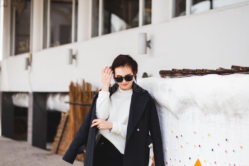 Modello grazioso della donna di modo che porta un cappotto scuro e un maglione bianco, in occhiali da sole, posanti sopra il fond immagini stock libere da diritti