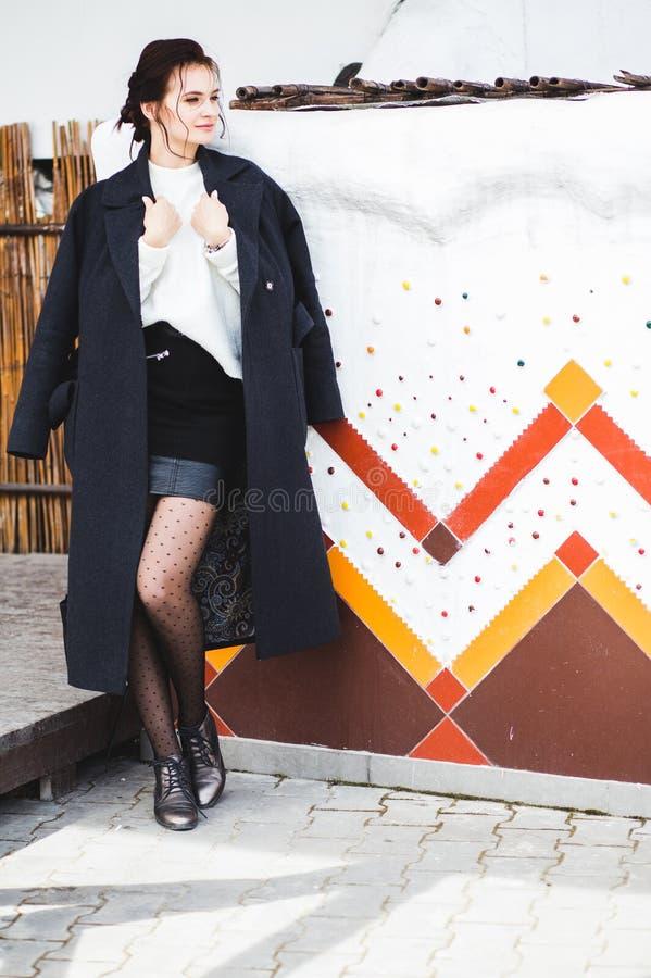 Modello grazioso della donna di modo che porta un cappotto scuro e un maglione bianco che posano sopra l'origine etnica fotografia stock