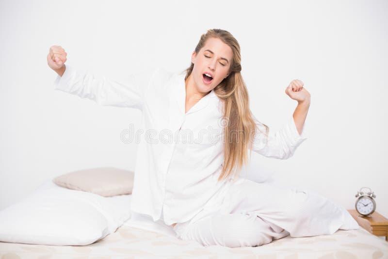 Modello grazioso di sbadiglio che allunga nel letto accogliente fotografie stock