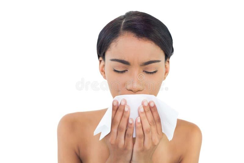 Modello grazioso malato che soffia il suo naso fotografia stock