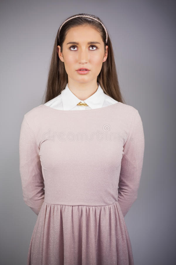 Modello grazioso serio con il vestito rosa sul cercare immagini stock