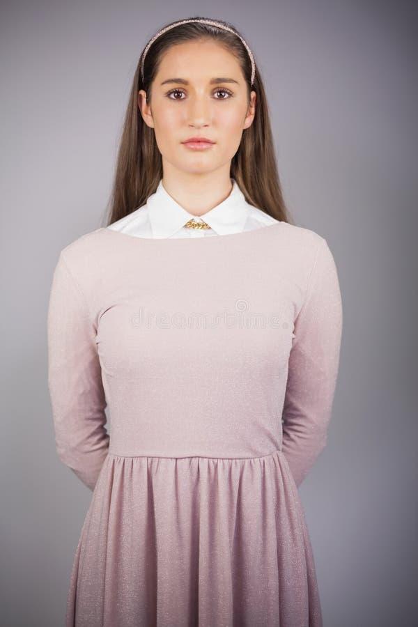 Modello grazioso serio con il vestito rosa sulla posa fotografia stock libera da diritti