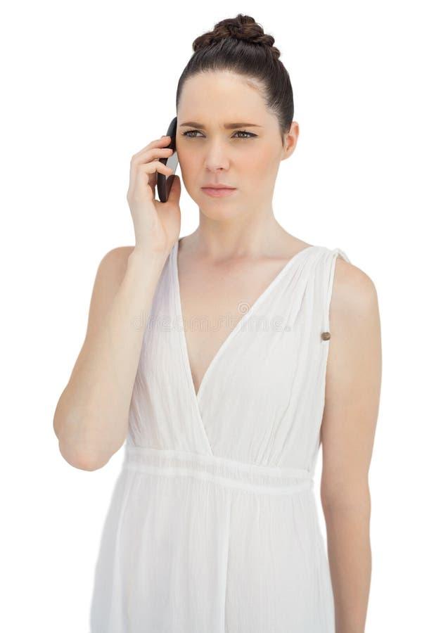 Modello grazioso serio in vestito bianco che ha telefonata fotografia stock libera da diritti