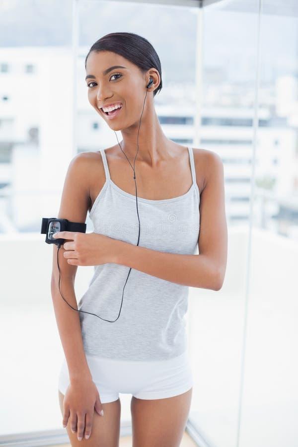 Modello grazioso sorridente nella canzone cambiante degli abiti sportivi sul suo mp3 immagini stock