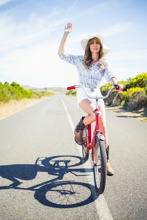 Modello grazioso sulla sua bici che fa gesto fotografia stock libera da diritti