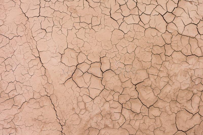 Modello incrinato di struttura della sabbia a terra asciutta del suolo desertico immagini stock