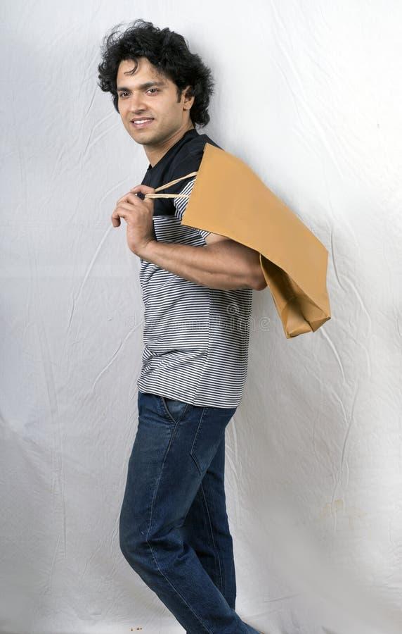 Modello maschio asiatico in maglietta nera con il sacchetto della spesa fotografia stock libera da diritti