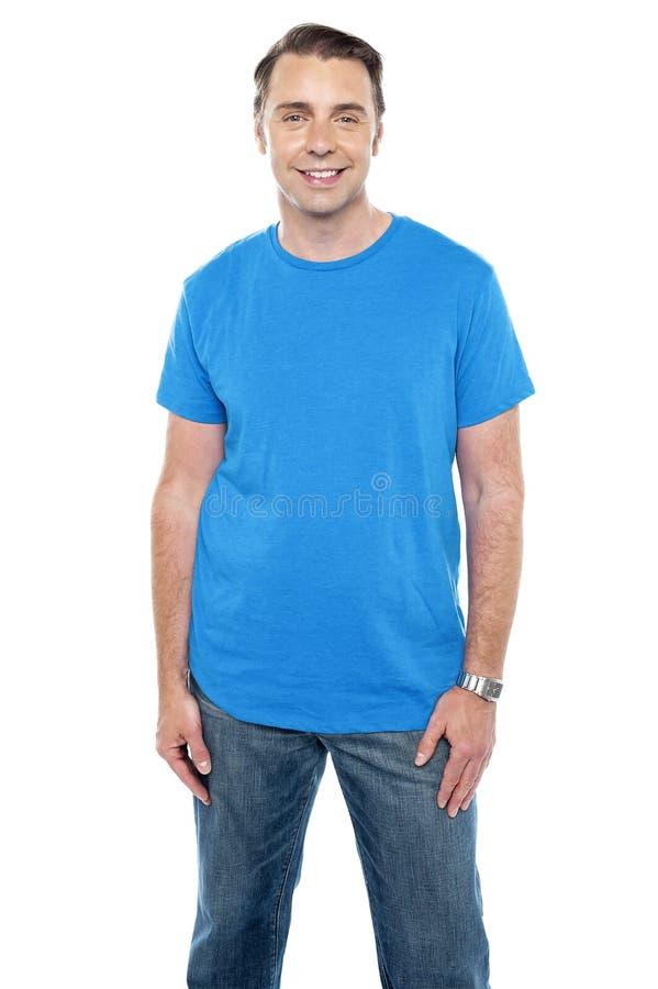 Modello maschio calmo allegro che propone nei casuals d'avanguardia immagini stock libere da diritti
