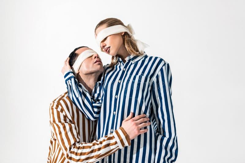 Modello maschio che abbraccia il suo collega biondo supplichevole fotografia stock