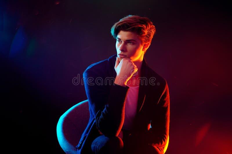 Modello maschio di alta moda alle luci al neon luminose variopinte che posano sul fondo nero concetto di progetto di arte immagini stock libere da diritti