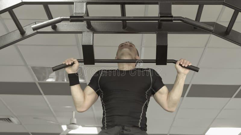 Modello maschio di forma fisica muscolare dell'atleta che tira su sulla barra orizzontale in una palestra immagini stock