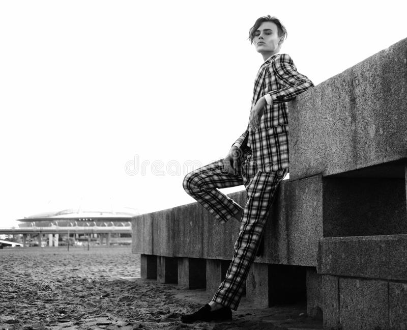 Modello maschio di modo bello vestito in vestito elegante che posa outdooe Metrosessuale dai capelli lunghi Maschera in bianco e  fotografie stock