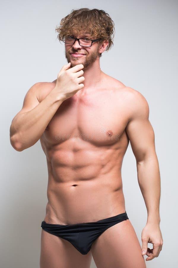 Modello maschio muscolare sexy che dura in vetri fotografia stock libera da diritti