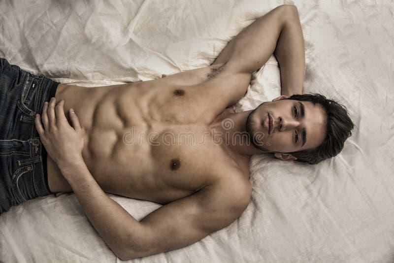 Modello maschio sexy senza camicia che si trova da solo sul suo letto fotografie stock