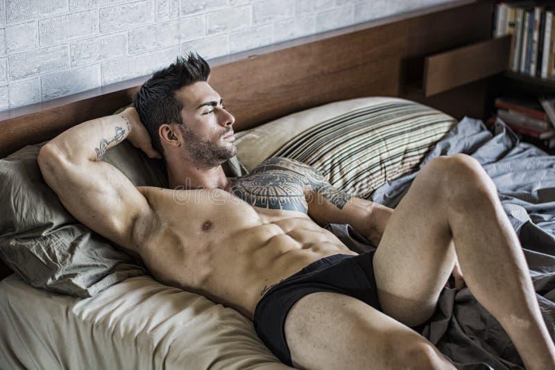Modello maschio sexy senza camicia che si trova da solo sul suo letto fotografie stock libere da diritti