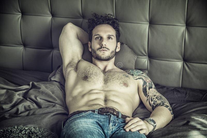 Modello maschio sexy senza camicia che si trova da solo sul suo letto fotografia stock