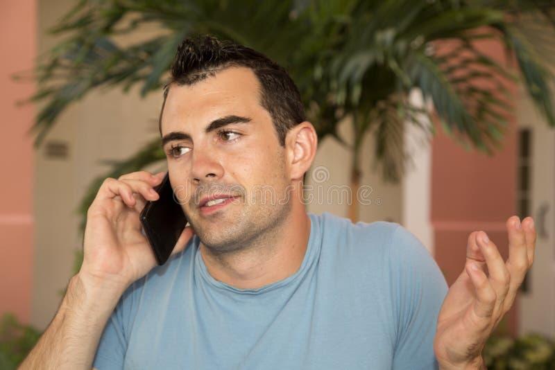 Modello maschio sul suo telefono cellulare che scrolla le spalle la sua interrogazione delle spalle fotografie stock libere da diritti