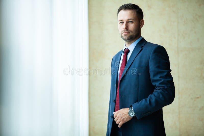Modello maschio in vestito di affari Le armi stanti del giovane uomo d'affari sicuro felice hanno attraversato, sorridere, esamin fotografia stock