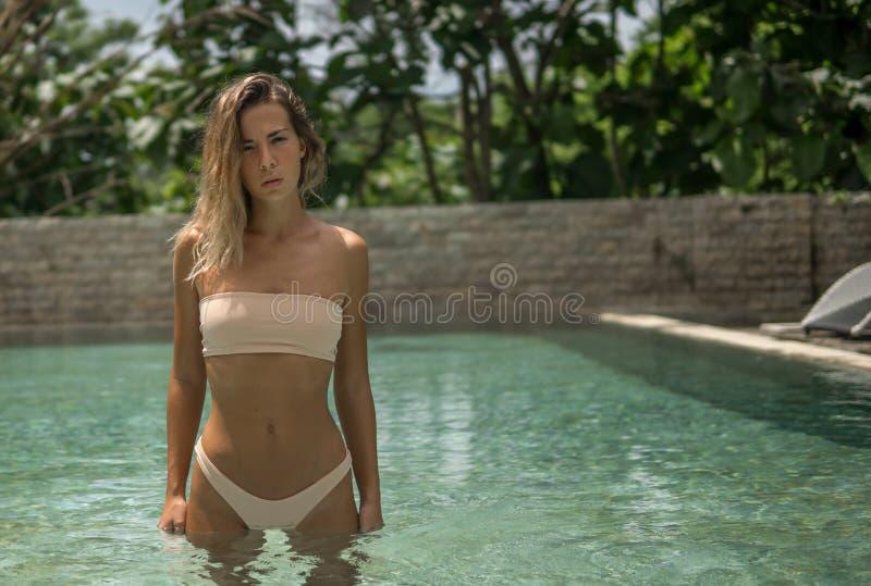 Modello meraviglioso in bikini rosa nella piscina fuori dell'hotel di località di soggiorno tropicale fotografia stock libera da diritti