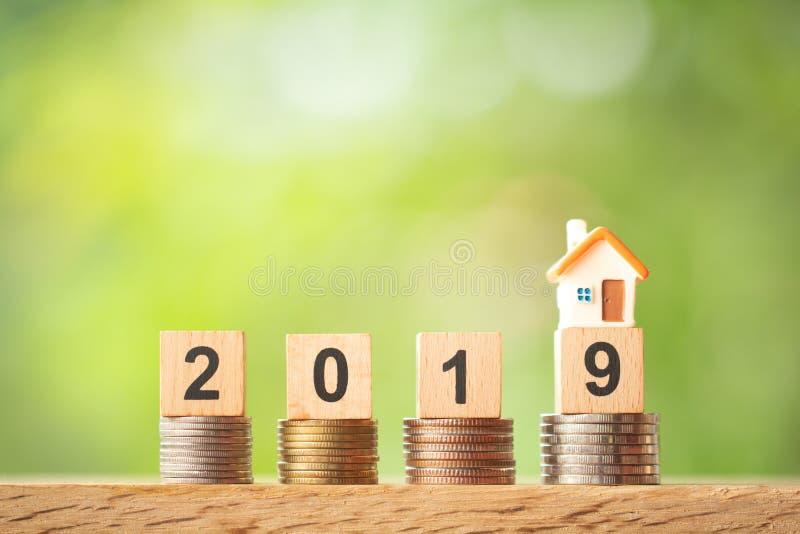 Modello miniatura della casa sull'anno 2019 sulle pile della moneta su fondo vago pianta fotografia stock libera da diritti