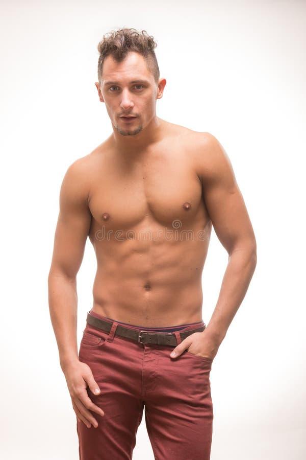 Modello muscolare dell'ente senza camicia dei pantaloni del giovane fotografia stock libera da diritti