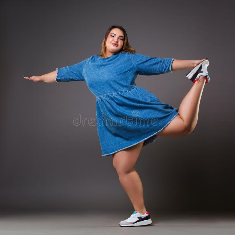 Modello più di dimensione in vestito dal denim, donna grassa su fondo grigio, ente femminile di peso eccessivo immagini stock libere da diritti