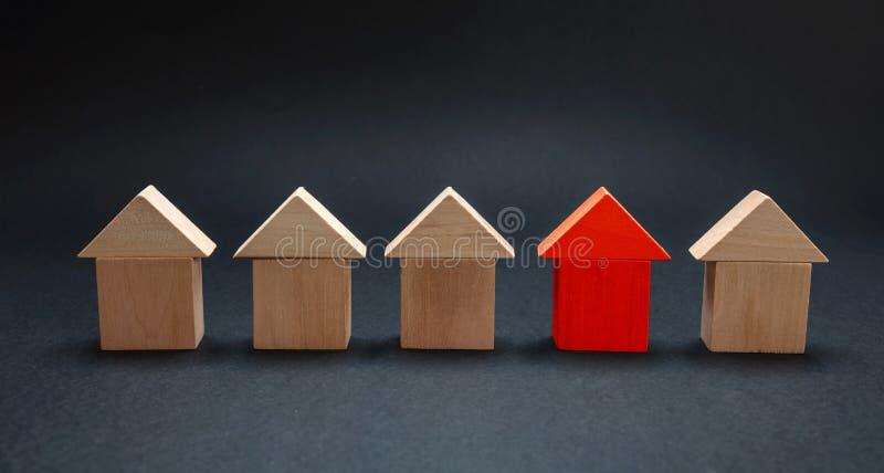 Modello rosso fra le case di legno, fondo nero della casa di colore fotografia stock libera da diritti