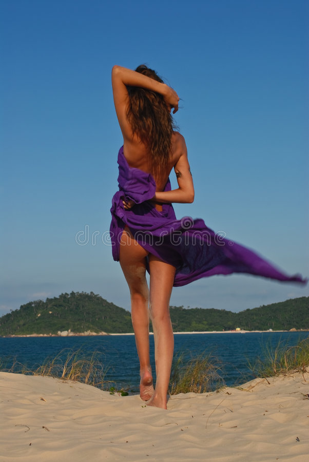 Modello sexy sulla spiaggia con il sarong viola fotografie stock
