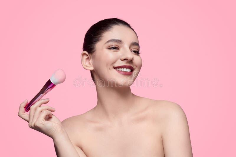 Modello sorridente con la spazzola di trucco fotografia stock libera da diritti