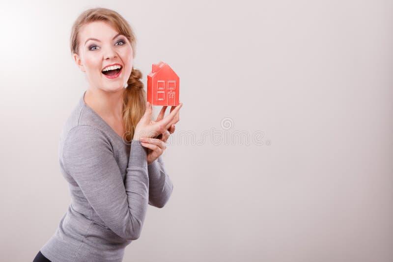 Modello sorridente della casa della tenuta della donna immagine stock