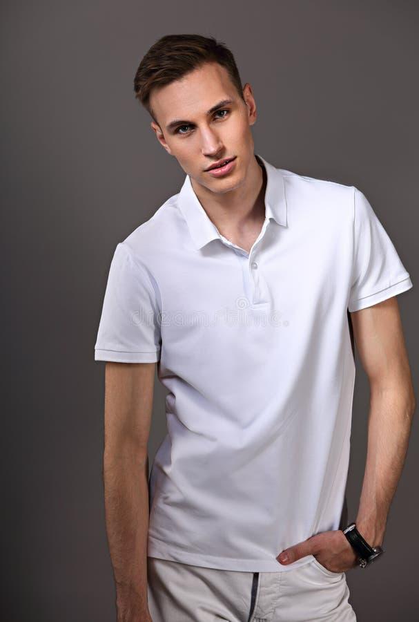 Modello sorridente maschio che posa in abbigliamento casuale di modo sul BAC grigio fotografia stock libera da diritti