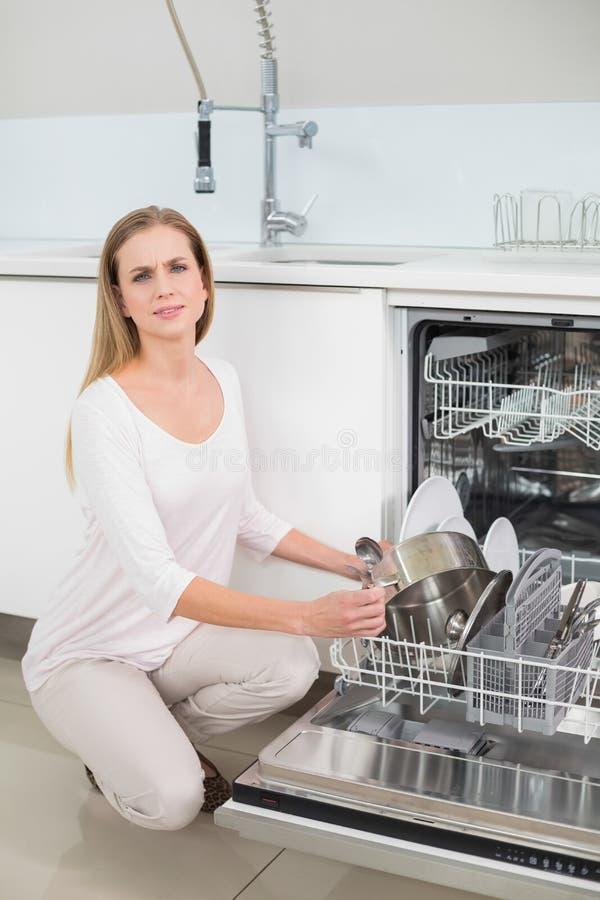 Modello splendido aggrottante le sopracciglia che si inginocchia accanto alla lavastoviglie immagini stock libere da diritti