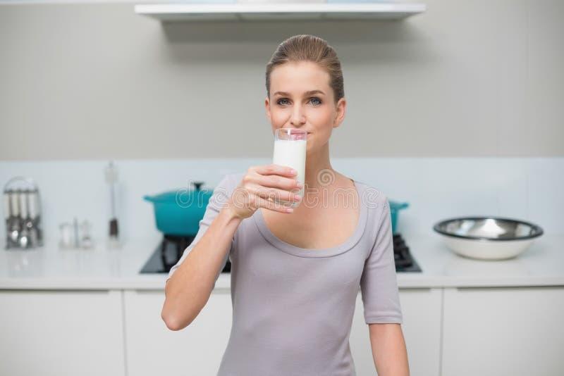 Modello splendido calmo che esamina il bicchiere della macchina fotografica di latte fotografia stock libera da diritti