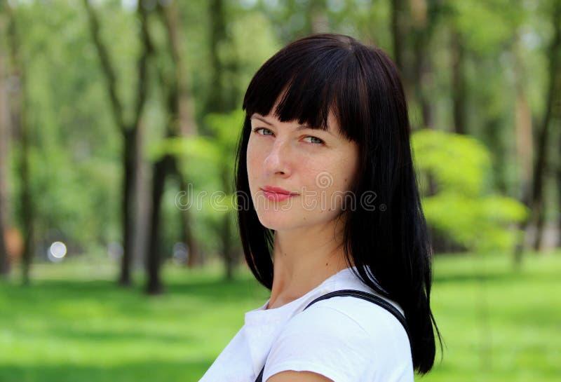 Modello splendido della giovane donna con capelli scuri che esaminano la macchina fotografica, posante nel parco in una maglietta fotografie stock libere da diritti