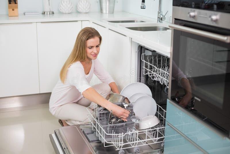 Modello splendido felice che si inginocchia dietro la lavastoviglie fotografia stock