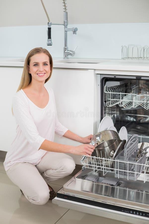 Modello splendido fortunato che si inginocchia accanto alla lavastoviglie immagine stock libera da diritti