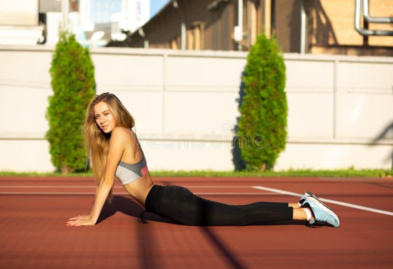 Modello sportivo dai capelli lunghi biondo bello che si esercita nel tenn fotografie stock libere da diritti