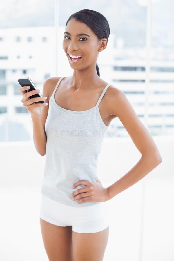 Modello sportivo felice facendo uso del suo smartphone fotografie stock libere da diritti