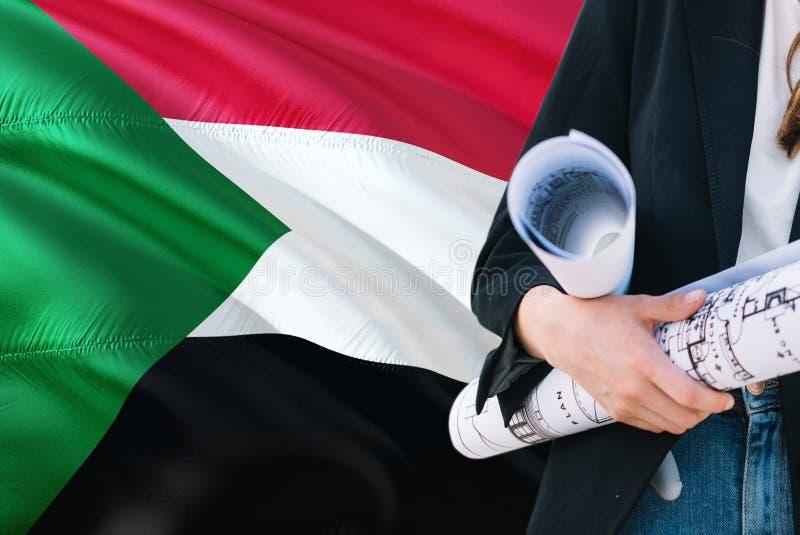 Modello sudanese della tenuta della donna dell'architetto contro il fondo d'ondeggiamento della bandiera del Sudan Concetto di ar fotografie stock libere da diritti