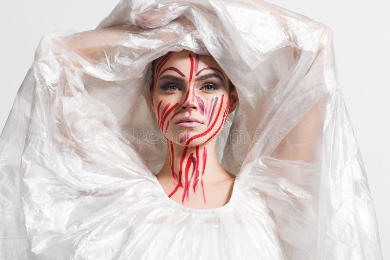 Modello in un impermeabile fatto di cellofan e nel trucco creativo fotografia stock