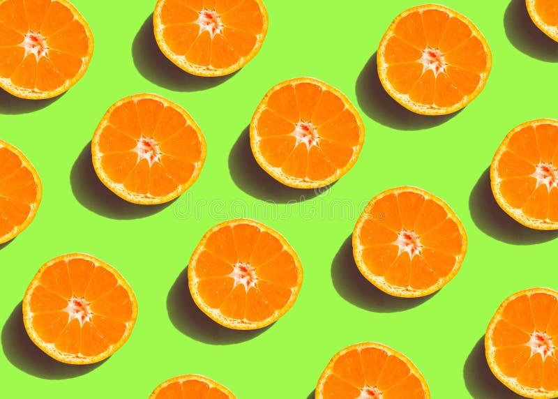 Modello variopinto della frutta delle fette arancio fresche su fondo verde fotografia stock
