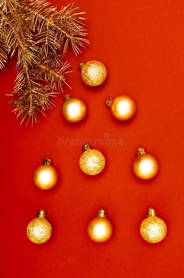 Modello verticale creativo con i rami dorati dell'albero di Natale e le bagattelle dorate multiple Concetto fotografie stock