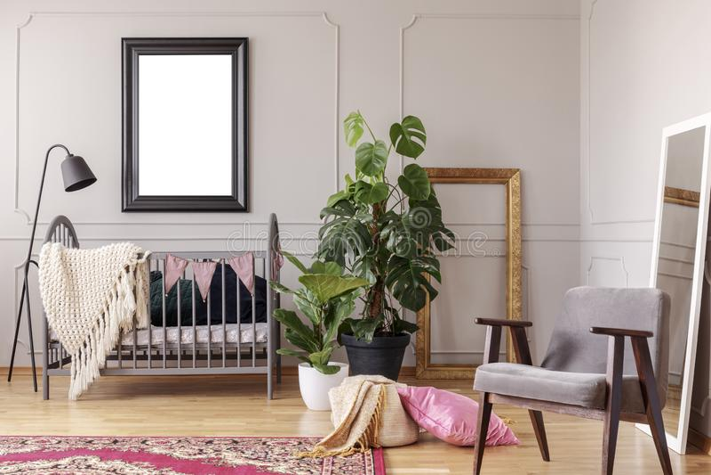 Modellplakat im grauen Babyrauminnenraum mit Grünpflanzen und Retro- Lehnsessel, stockfotografie