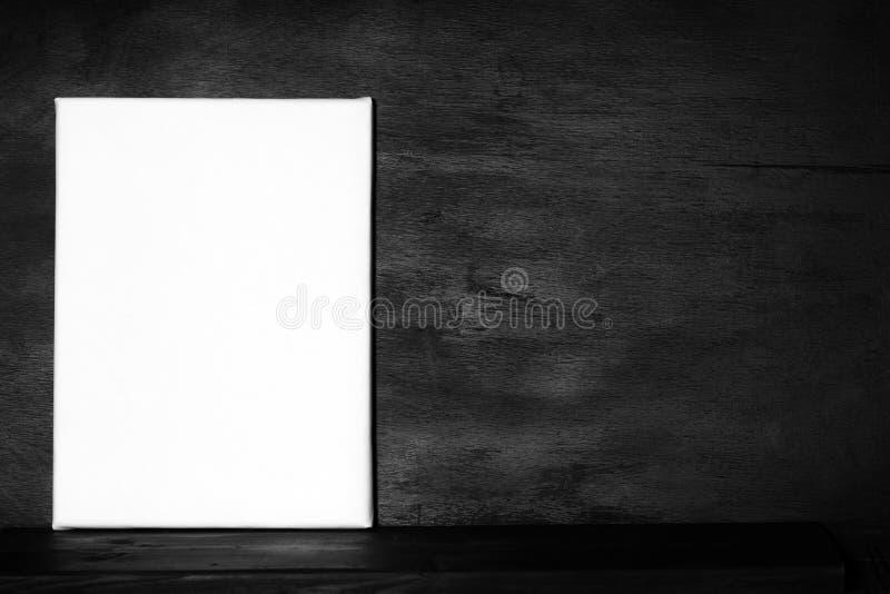 Modellplakatrahmen Leeres Segeltuch im schwarzen Innenraum stockbild