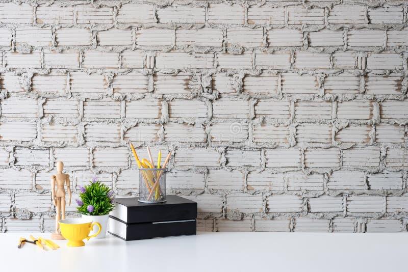 Modelltabell med koppen kaffe, boken, den träfalska modellen och kruset av blyertspennan på vit tabell- och tegelstenväggbakgrund royaltyfria bilder