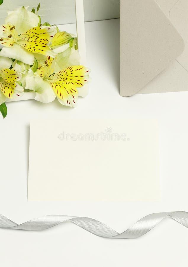 Modellvisitenkarten auf weißem Hintergrund, frischen Blumen und Rahmen stockfotos