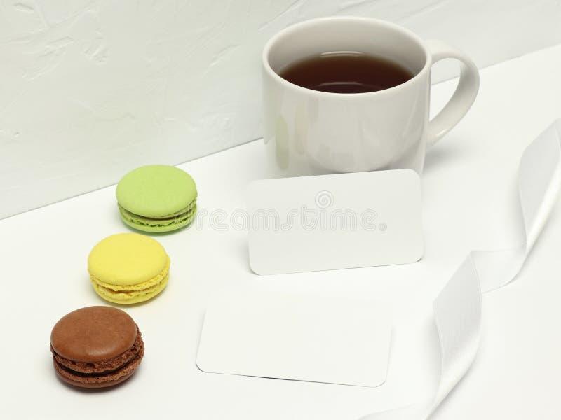 Modellvisitenkarten auf wei?em Hintergrund mit macaron, Band und Tasse Kaffee stockbilder