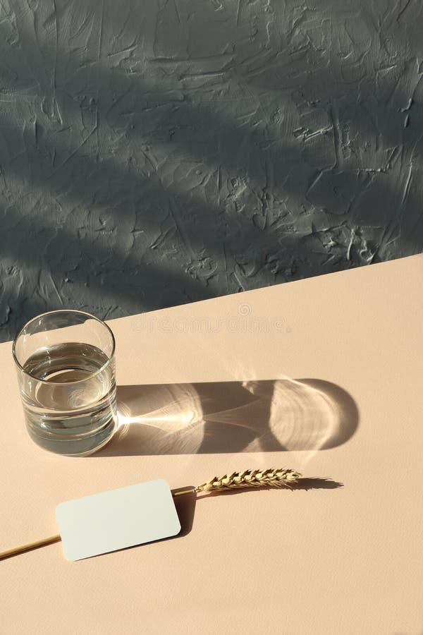 Modellvisitenkarten, Wheatear, Glas auf beige Hintergrund lizenzfreie stockbilder