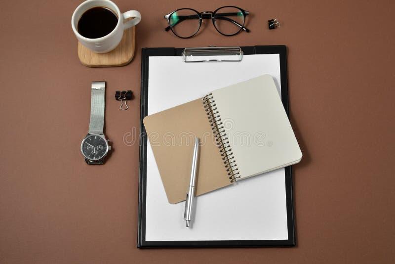Modellworkspace med det tomma gembrädet, kontorstillförsel, klockan, pennan, kaffekoppen, notepaden och glasögon på brun bakgrund fotografering för bildbyråer